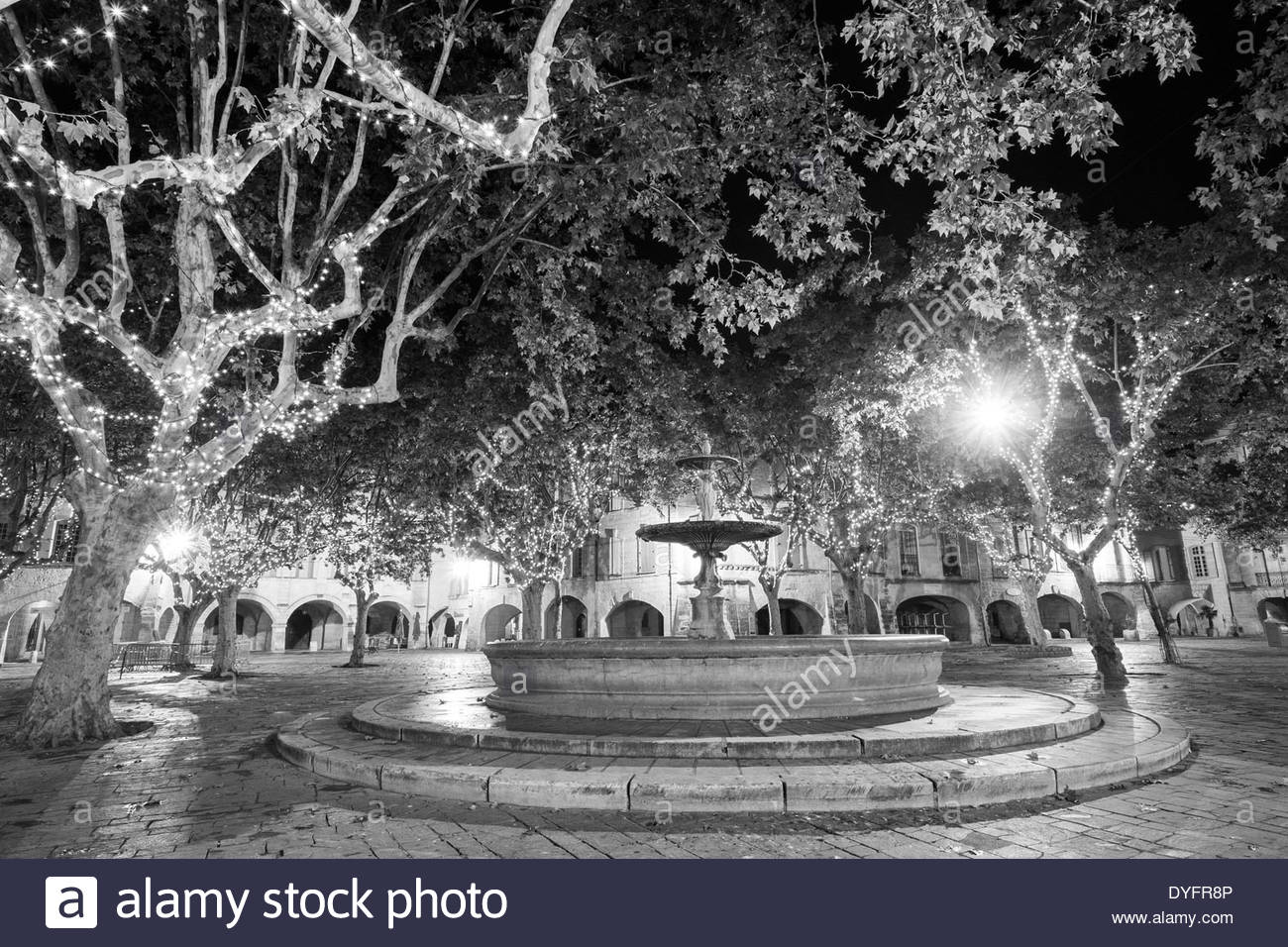 Fountain and lights on Place aux Herbes at night, Uzès, Gard Department, Languedoc-Roussillon, France - Stock Image