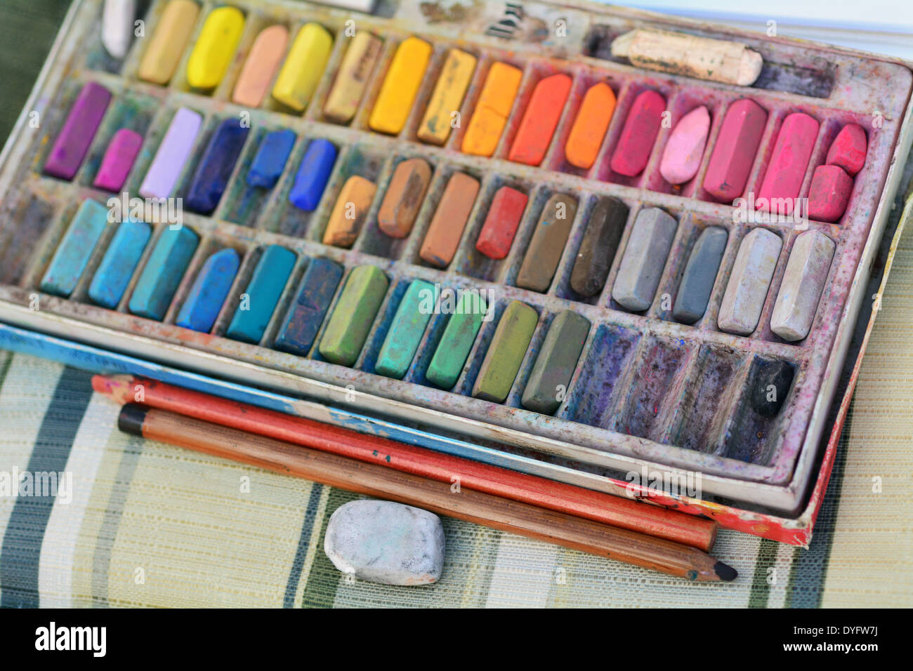 Panel set of used colorful chalk colors with pencils and rubber on artist chair. - Stock Image