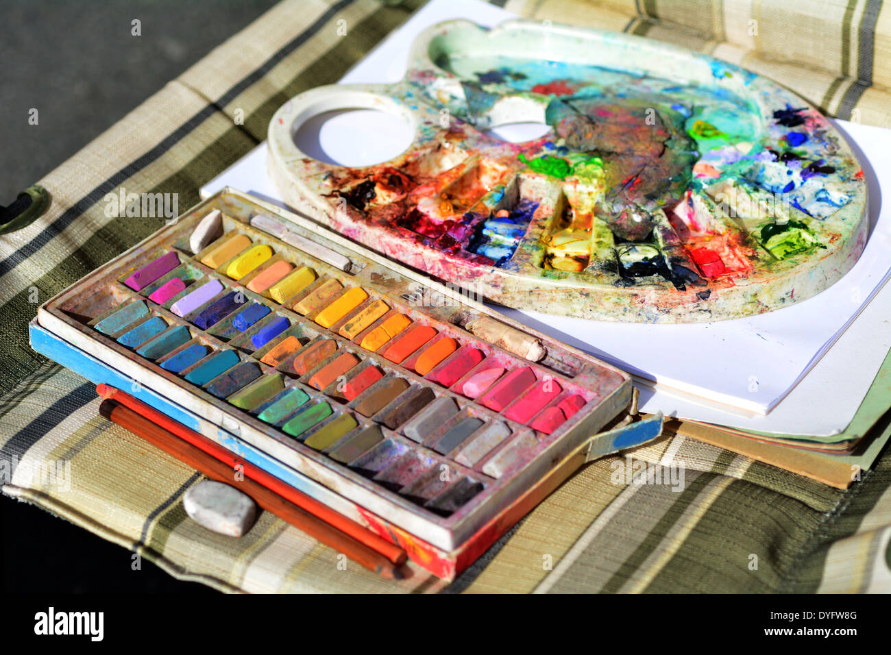Used colorful chalk colors and colors pallet on artist chair. - Stock Image