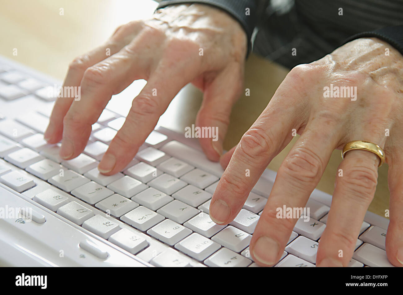 senior woman hands on computer keyboard - Stock Image