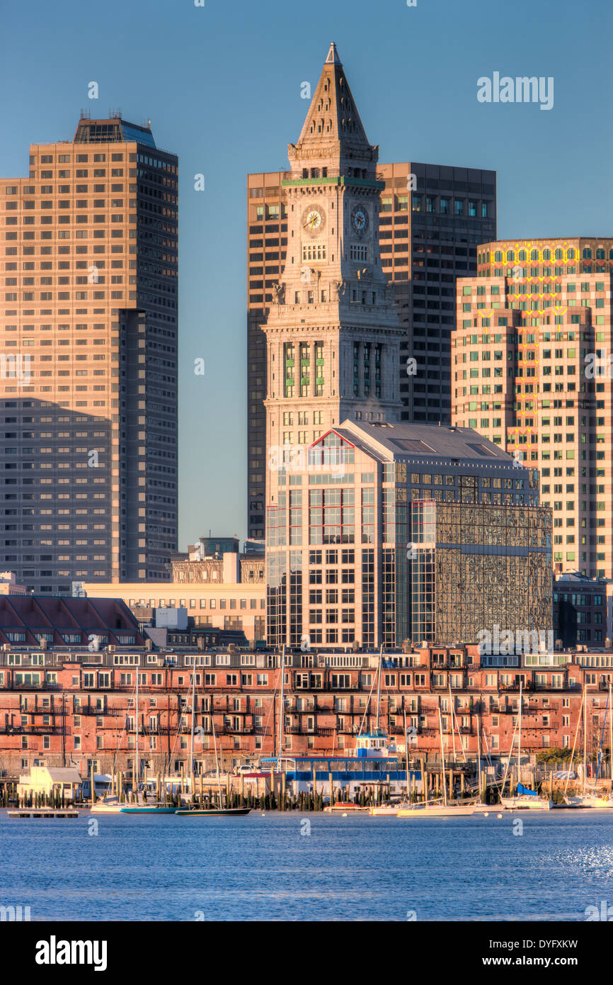 A morning view of the Custom House Tower, the Financial District, and low rise wharves on the waterfront in Boston, Massachusetts. - Stock Image