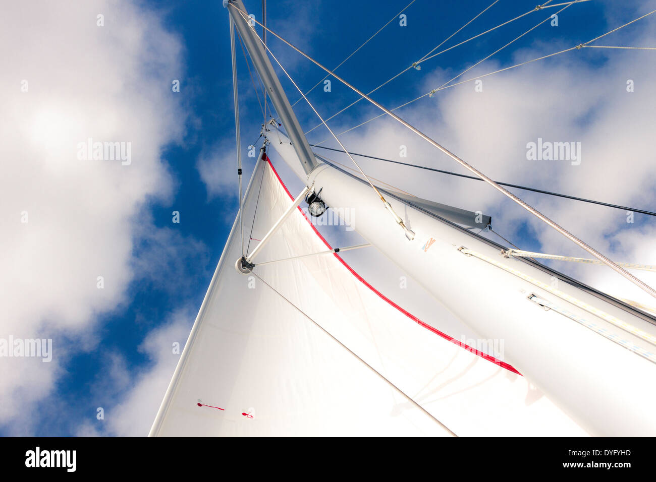 Looking up at white sail and mast of a sailboat against a blue sky with clouds - Stock Image