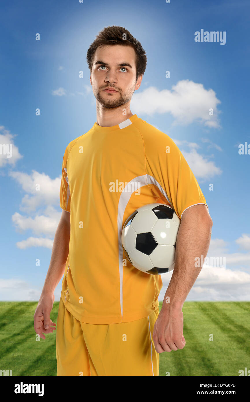 Portrait of soccer player holding ball isolated outdoors during sunny day - Stock Image