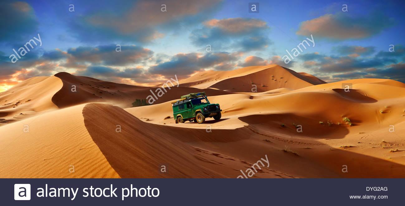 4 x4 Landrover Defnder on the Sahara sand dunes of erg Chebbi at sunset , Morocco, Africa - Stock Image