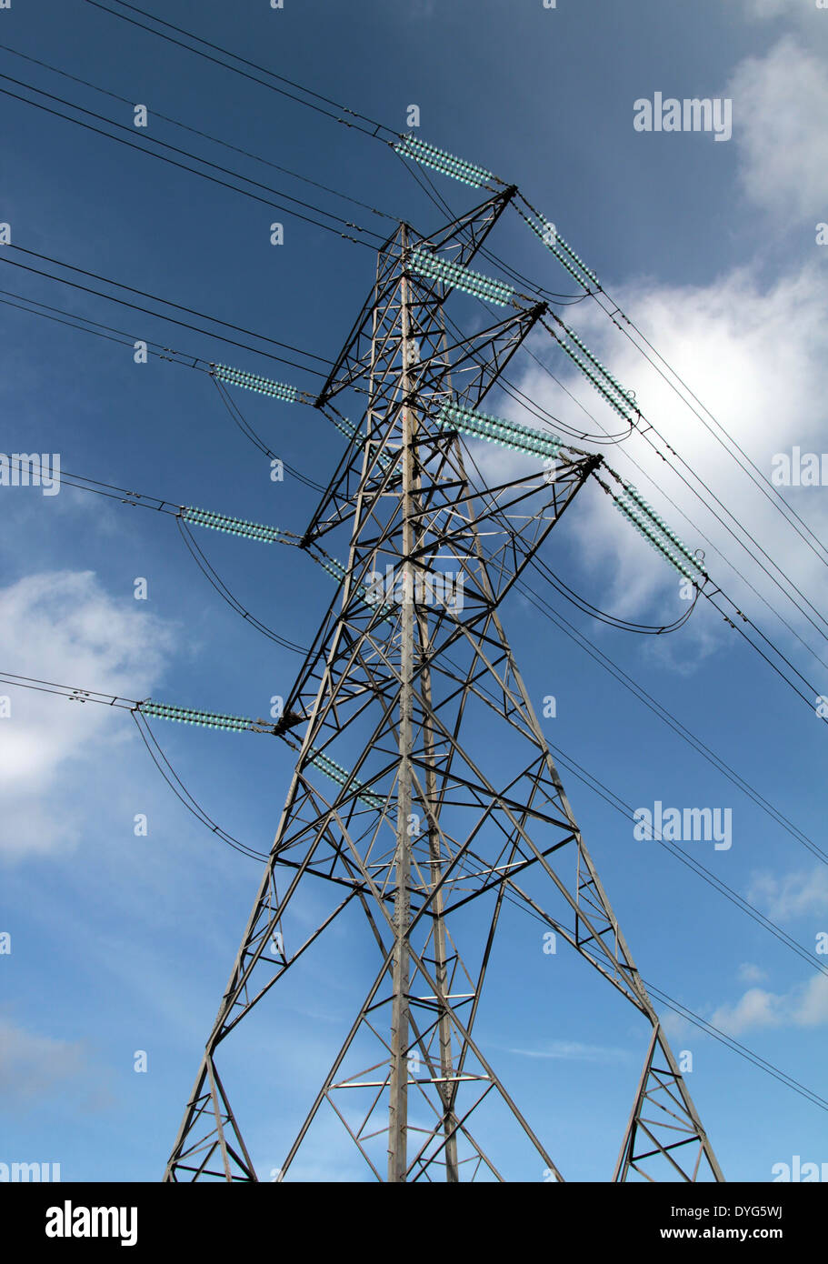 An electricity pylon against a blue sky. - Stock Image
