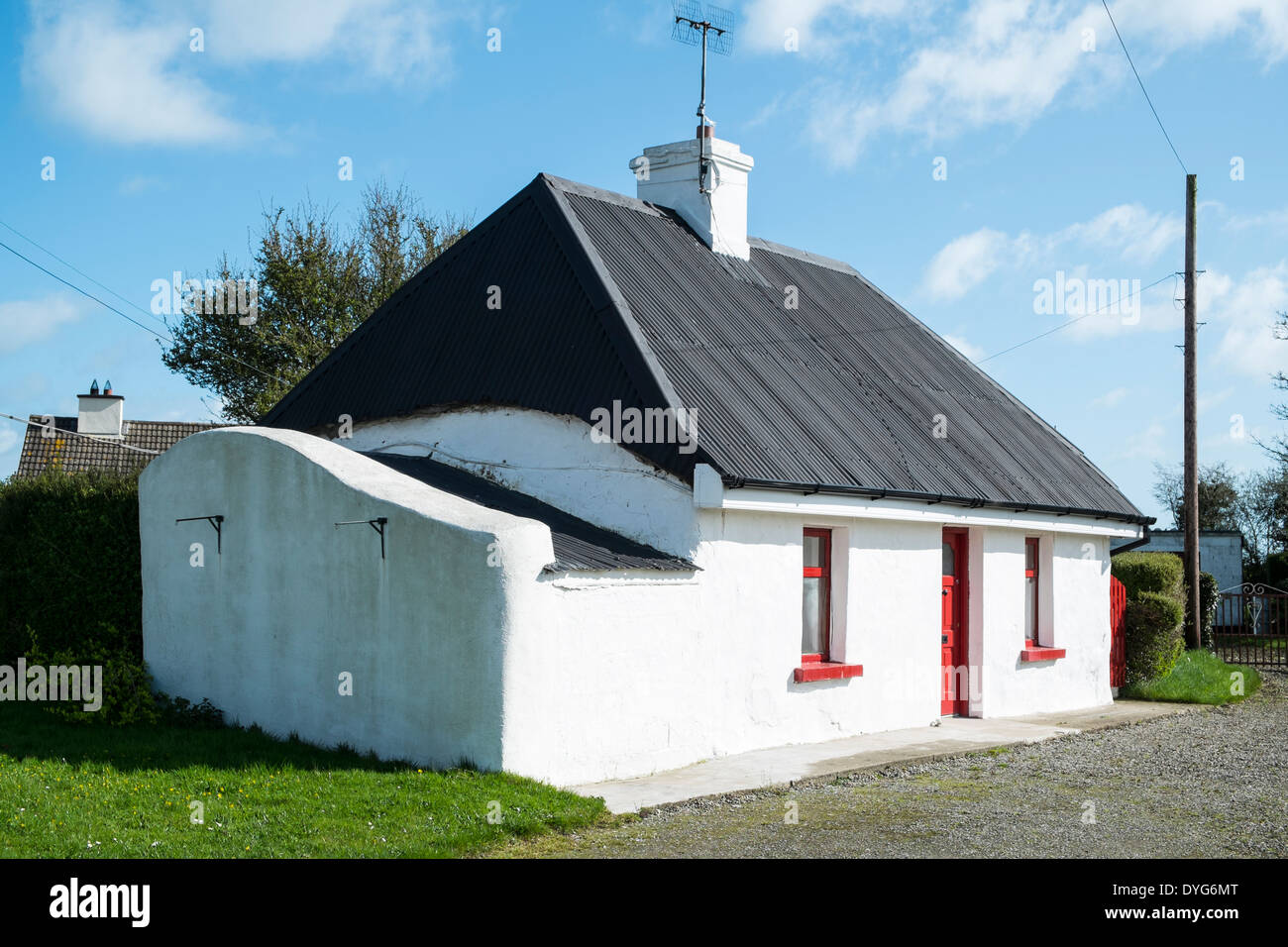 An old cottage, originally thatched but now with a corrugated iron roof on top, quite traditional - Balscadden, - Stock Image