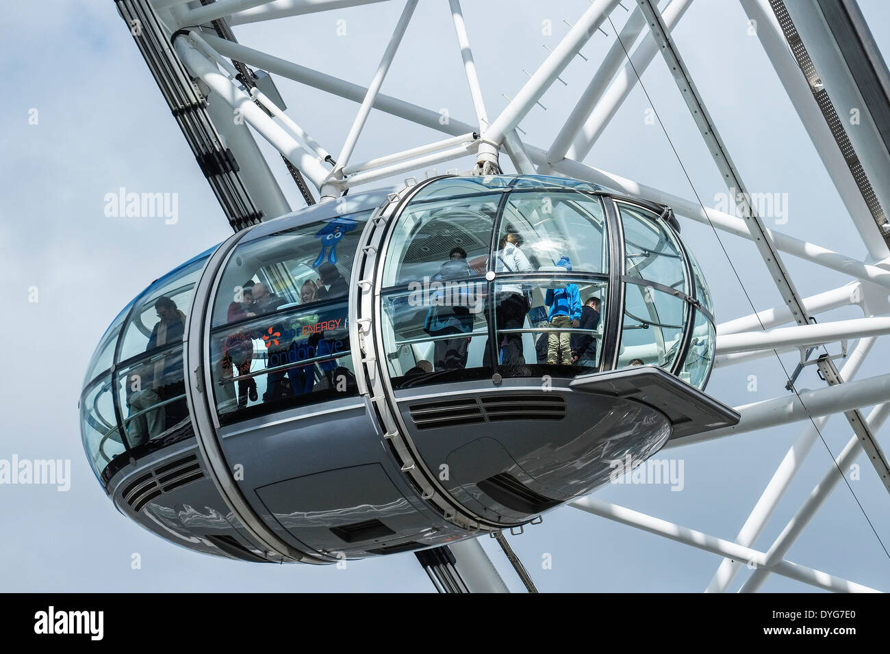 Tourists enjoying riding in a passenger capsule of the London Eye. - Stock Image