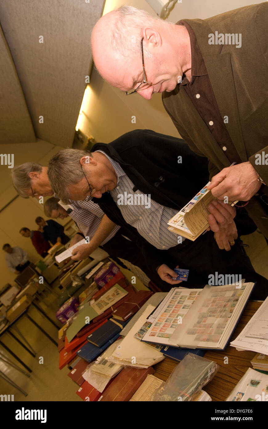 People attending a stamp auction, Petersfield, Hampshire, UK. - Stock Image
