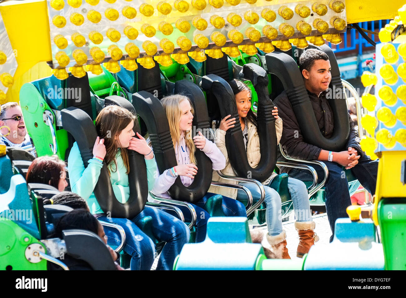 People waiting for a fairground ride to start. - Stock Image