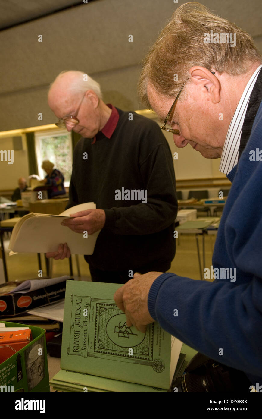 Elderly men attending a stamp auction and perusing items to be sold, Petersfield, Hampshire, UK. - Stock Image