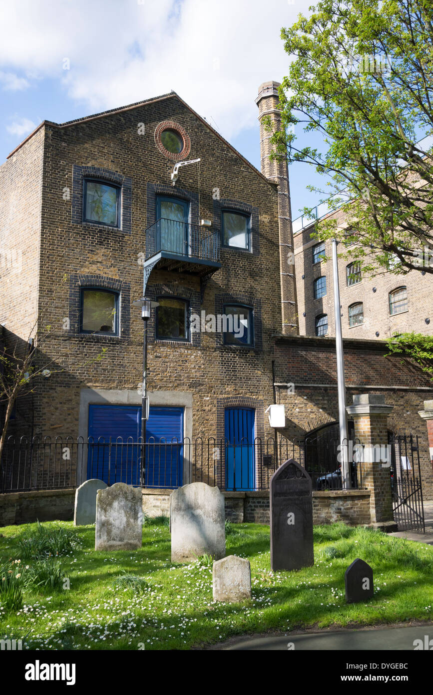Tombstones in churchyard of Saint Mary the Virgin Church and wharf building, Rotherhithe, London, UK - Stock Image