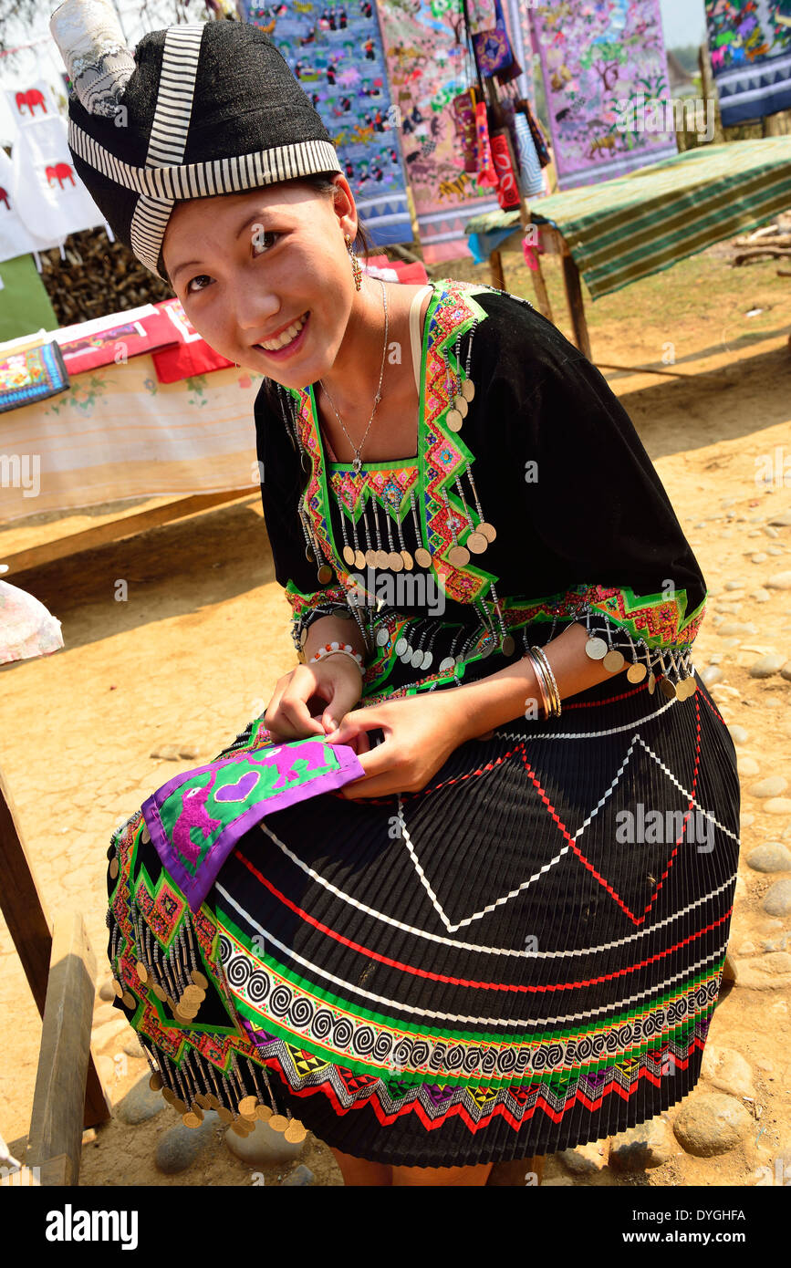 Hmong girl at work embroidering cloth to be made into purses for tourists , open air market, a village near Luang Prabang ,Laos - Stock Image