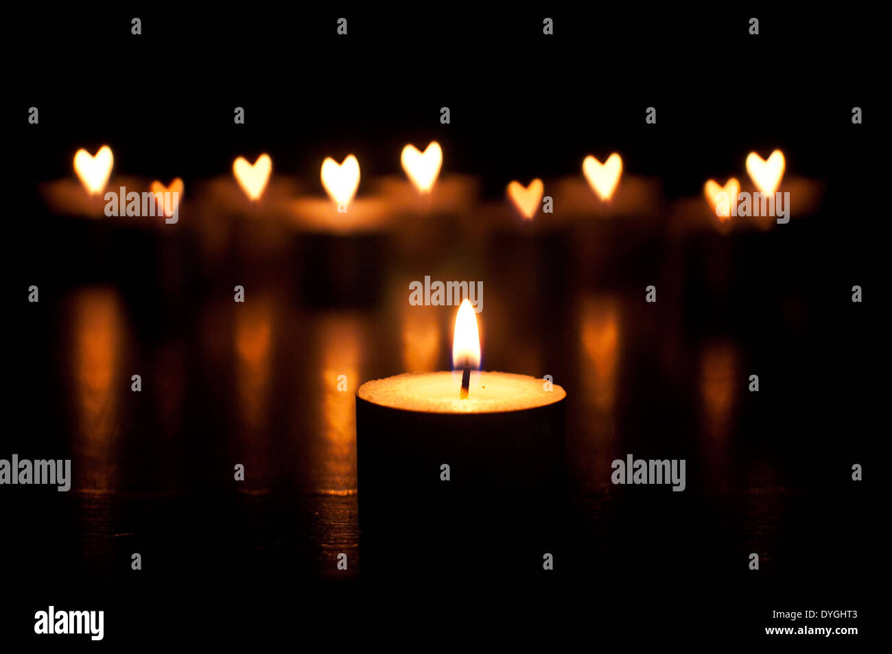 candles with out of focus flames in the shape of love hearts - Stock Image