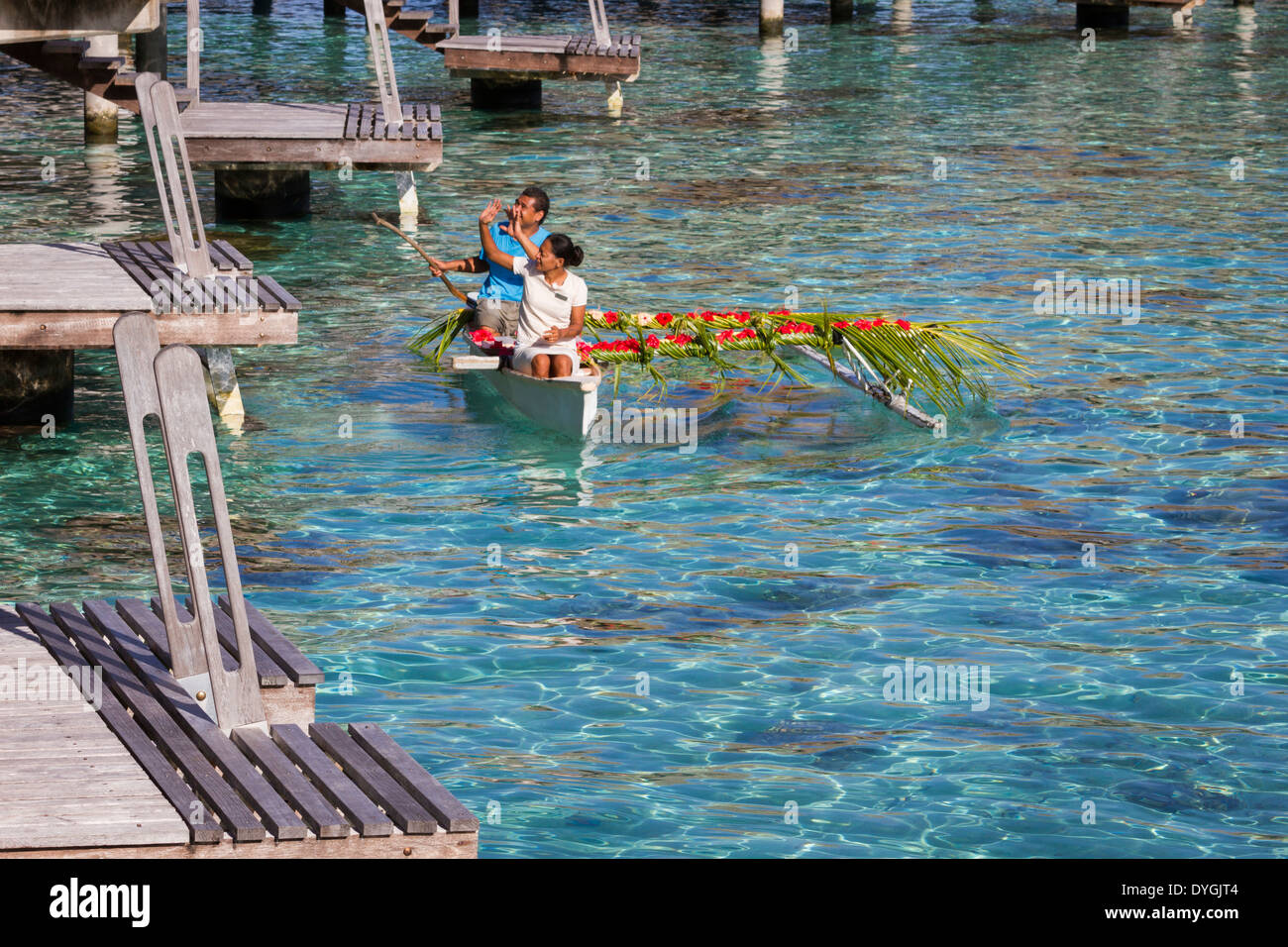 Polynesian people delivering room service in a canoe to overwater bungalow at a resort in French Polynesia - Stock Image