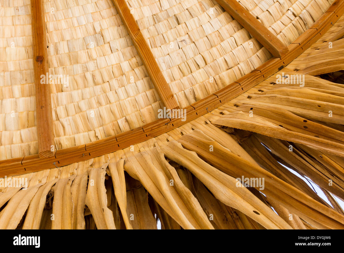 Closeup of round thatched roof hut showing structure of woven palm thatch - Stock Image