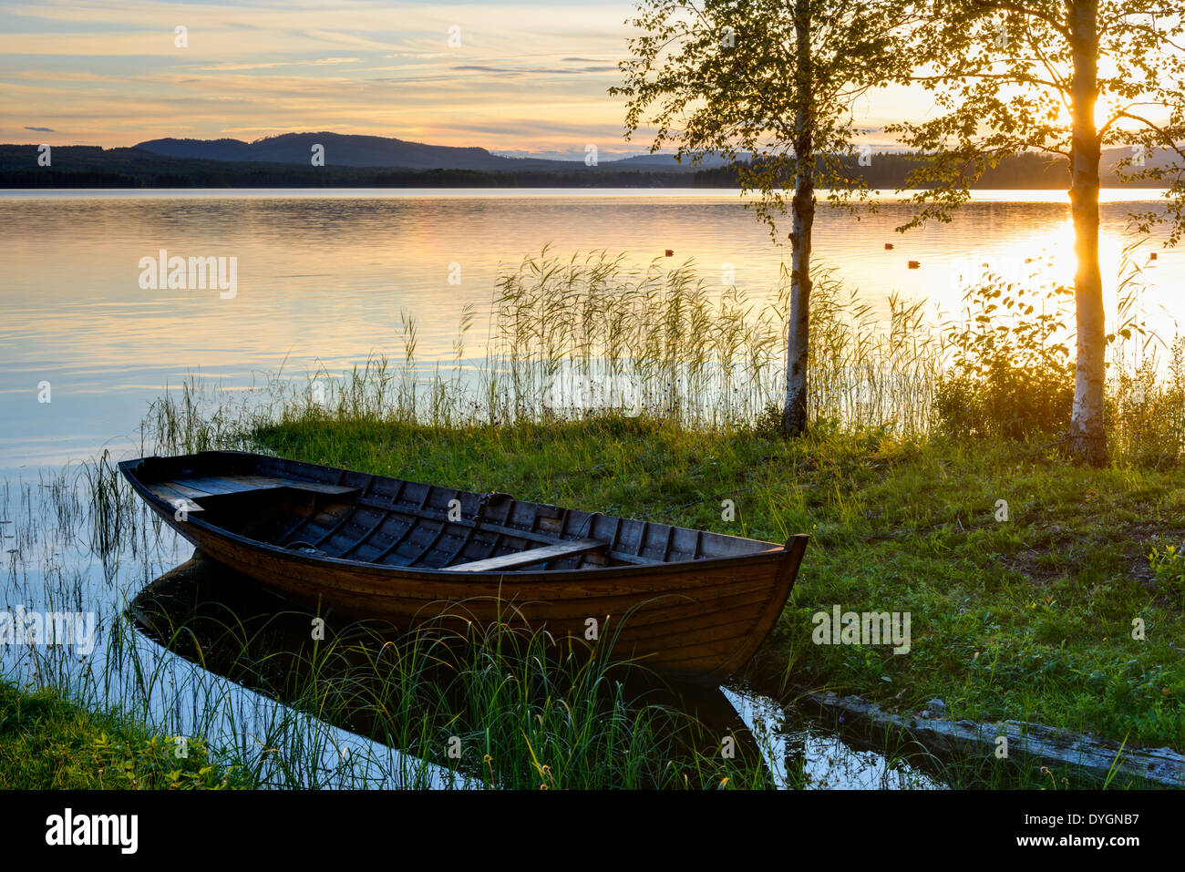 Wooden boat at the lakeside at sunset, Solleron, Dalarna, Sweden - Stock Image