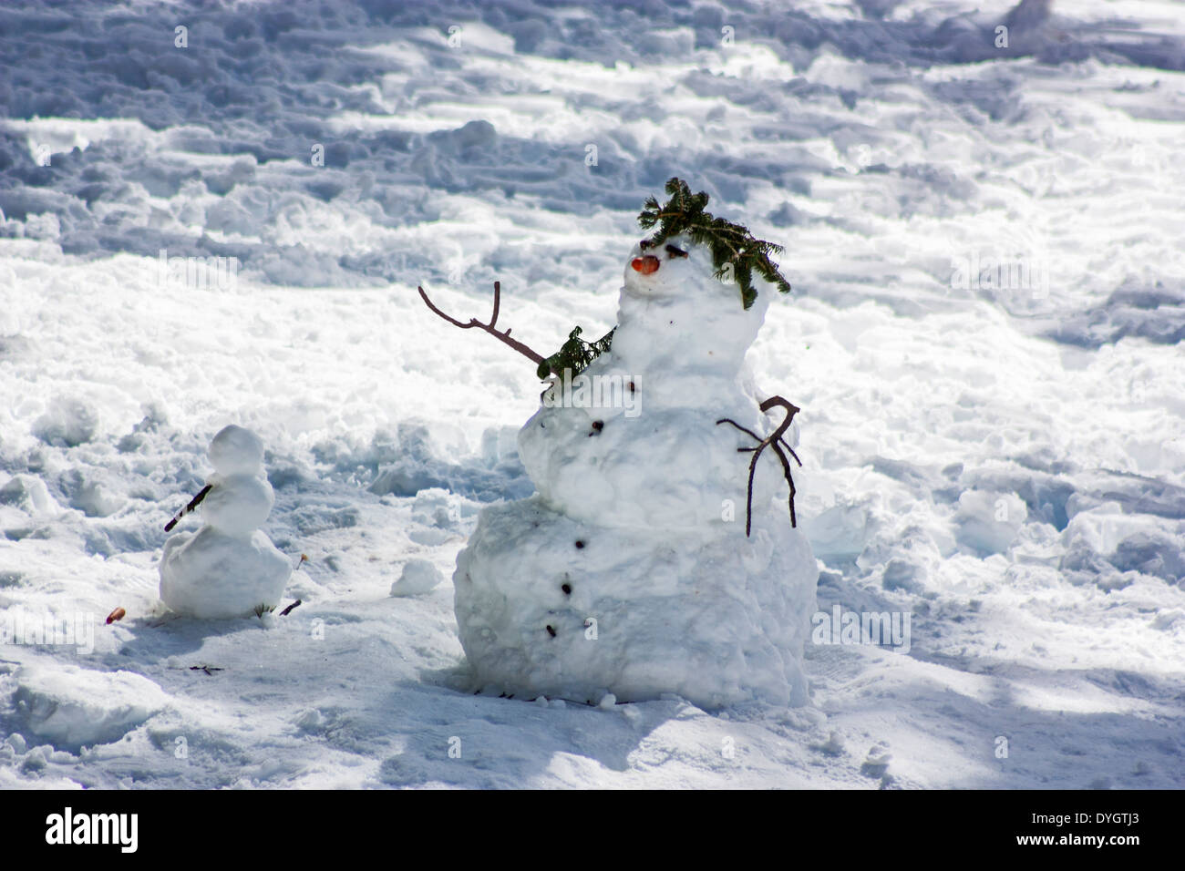 Mount San Jacinto, Palm Springs, California, a large snowman stands over a smaller partially built snowman with arm raised - Stock Image