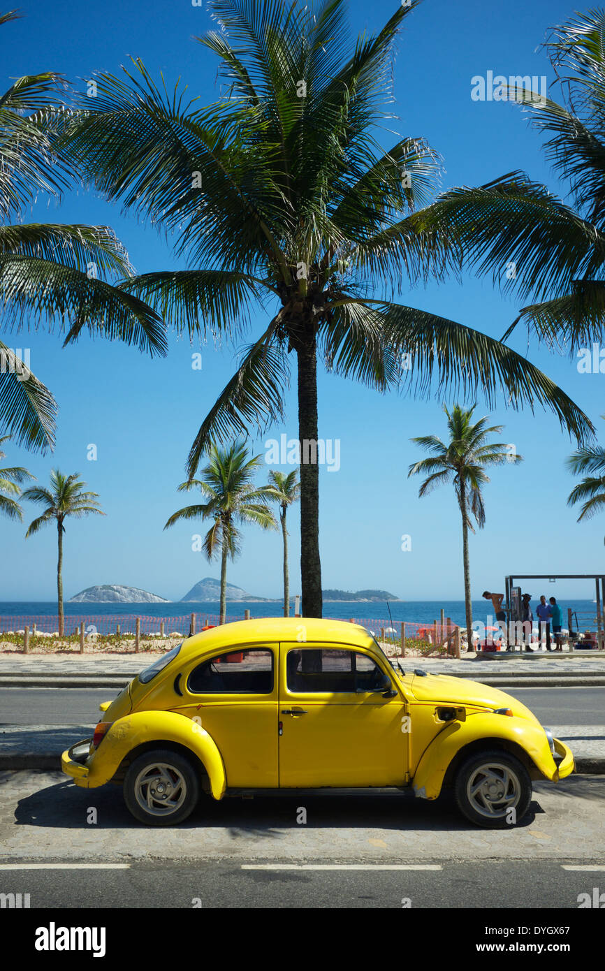 RIO DE JANEIRO, BRAZIL - FEBRUARY 6, 2014: Old yellow Volkswagen Type 1 Beetle, known locally as a Fusca, parked in front of Ipa - Stock Image