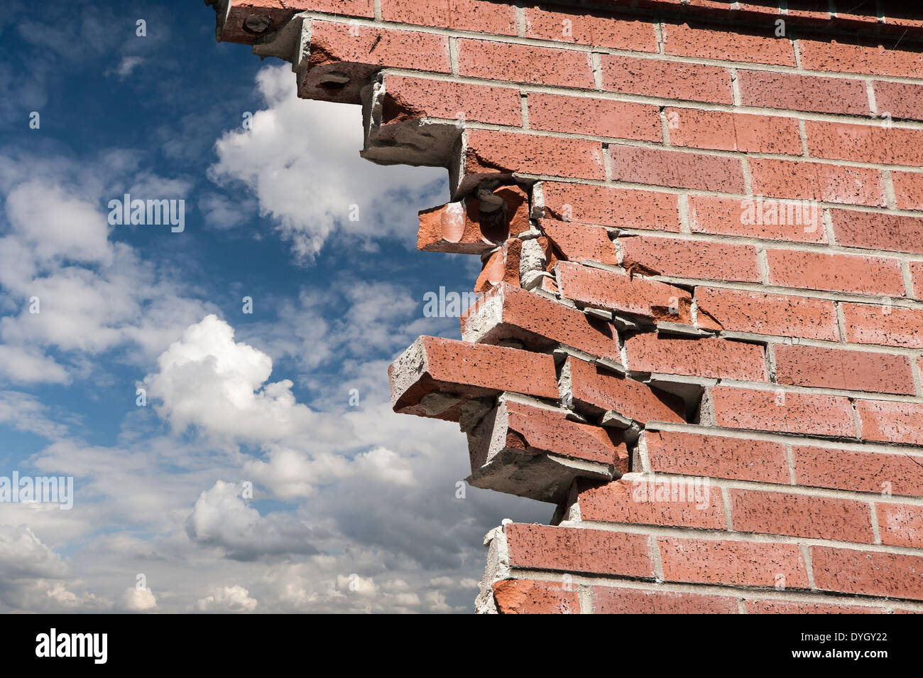 Broken brick wall and blue sky with clouds. - Stock Image