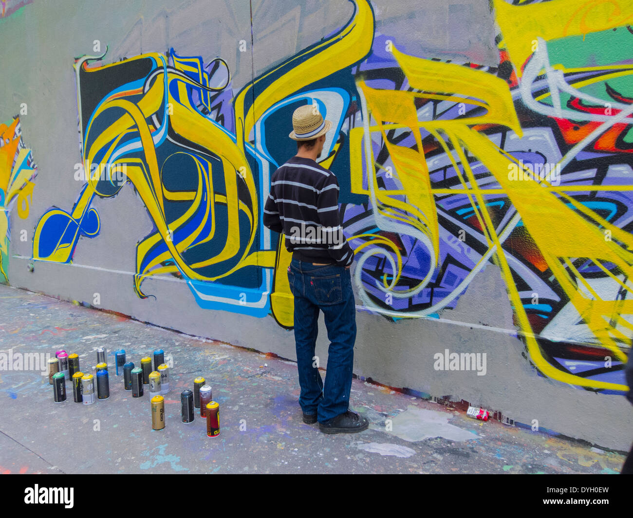 Paris france young french teen graffiti artist painting wall on street modern abstract art