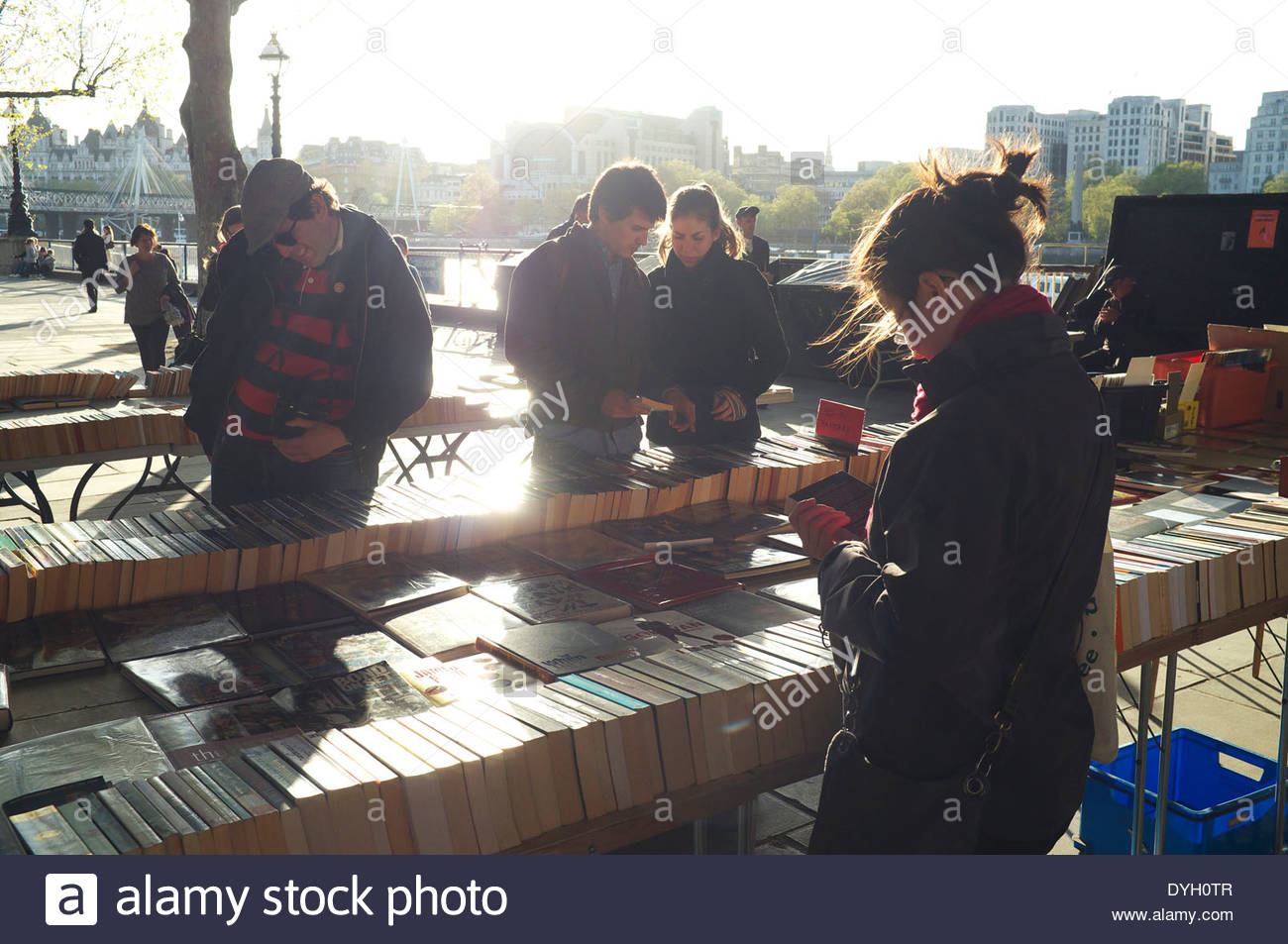 Evening light bounces off the second hand bookstall underneath Waterloo Bridge. South Bank, London, UK. - Stock Image