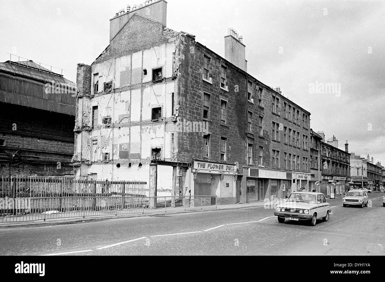 Tenements being demolished on Glasgow Road, Clydebank, with very little thought to health and safety. Shipyard buildings behind - Stock Image