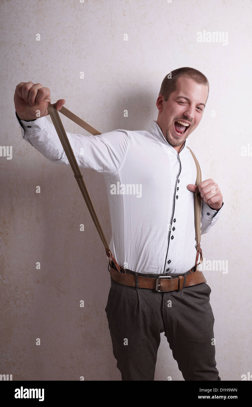 young man messing with suspenders - Stock Image