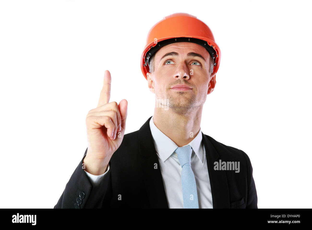 Portrait of a businessman in helmet pointing up at copyspace over white background - Stock Image
