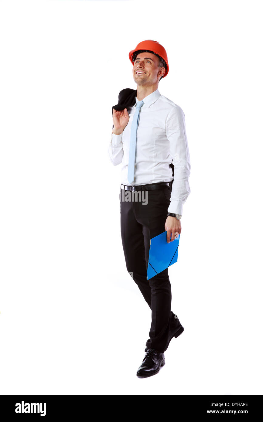 Happy businessman in helmet with blue folder over white background - Stock Image
