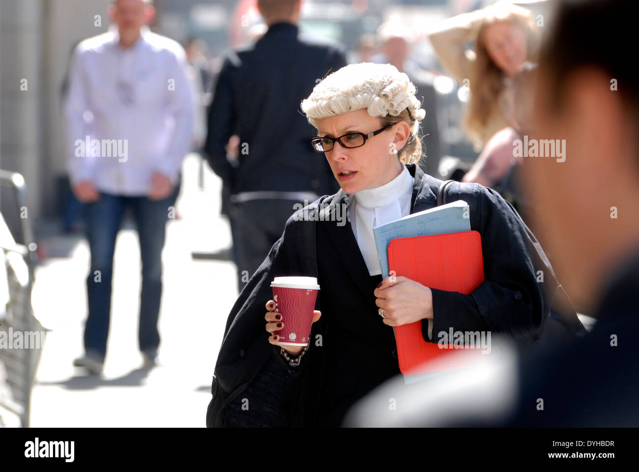 London, England, UK. Female barrister carrying a cup of coffee outside the Central Criminal Court, Old Bailey - Stock Image