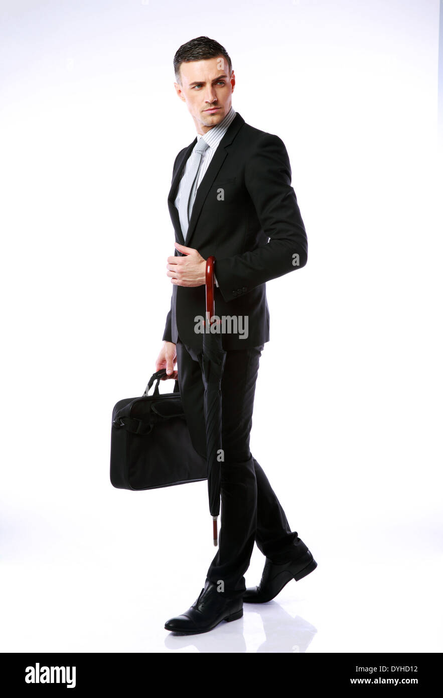 Full-length portrait of a confident businessman standing with umbrella and laptop bag - Stock Image