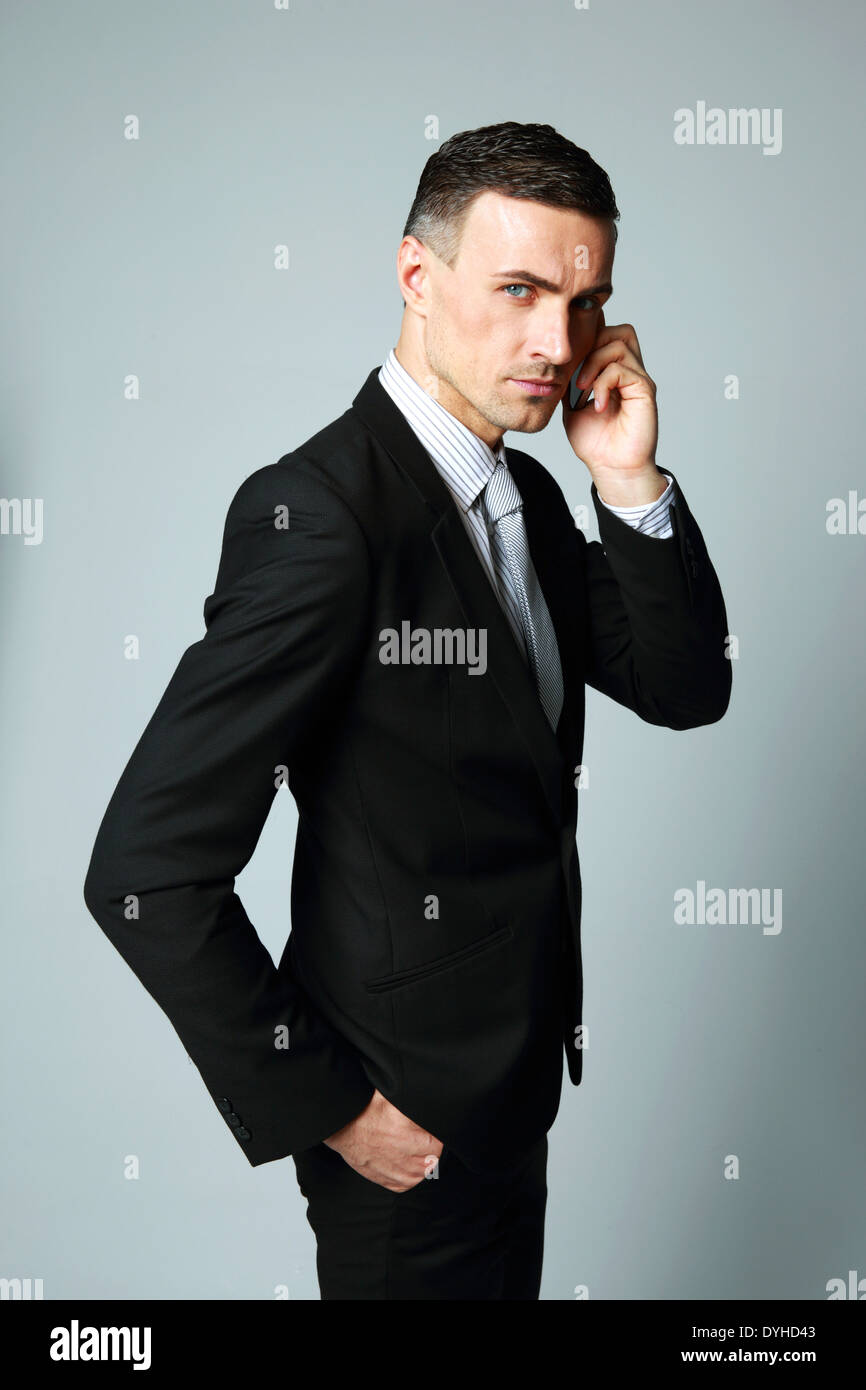 Confident businessman talking on his mobile phone on gray background - Stock Image