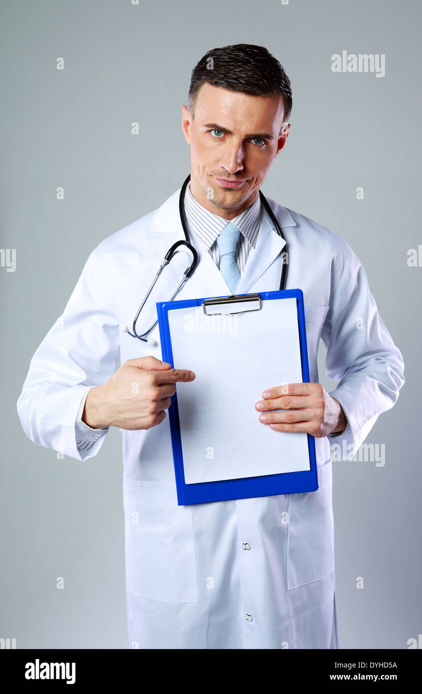 Dissatisfied male doctor showing on empty clipboard on gray background - Stock Image