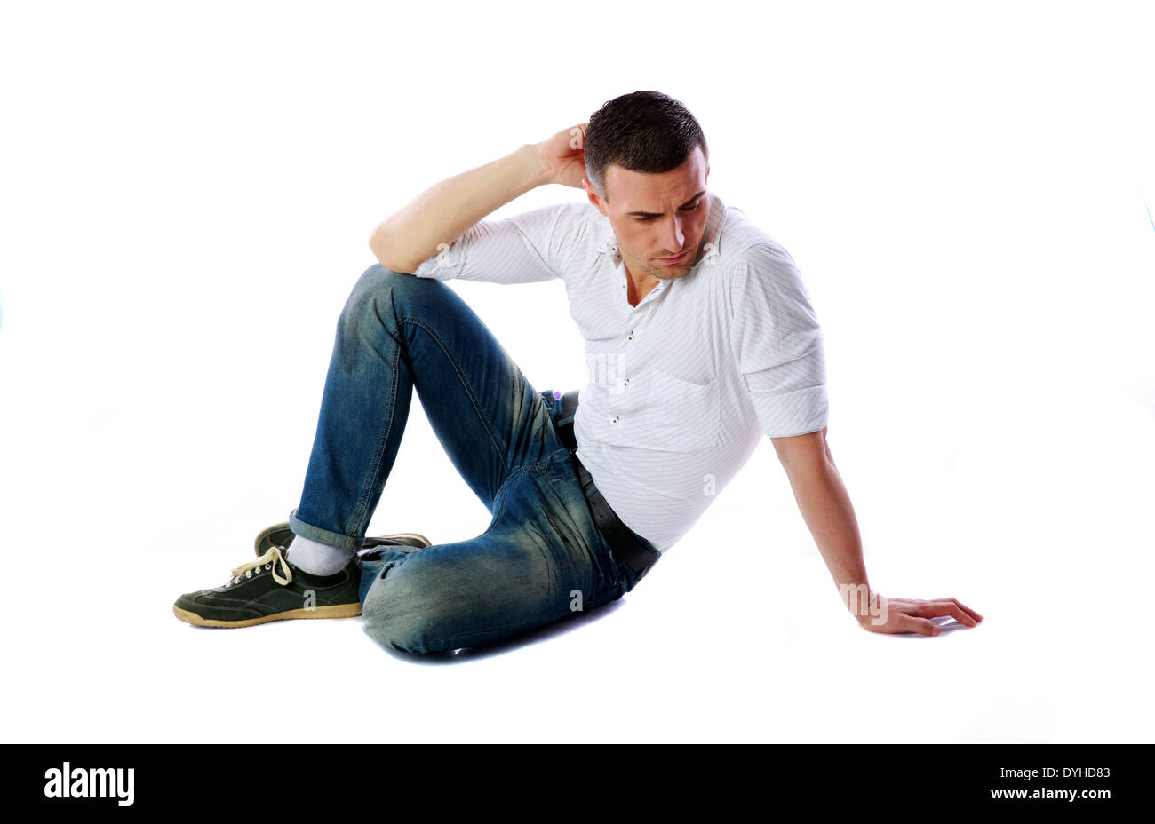 Pensive man sitting at the floor over white background - Stock Image