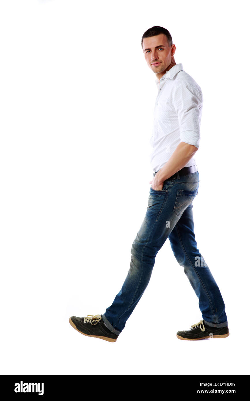ffdeacbef607 Side view portrait of a casual man walking over white background ...