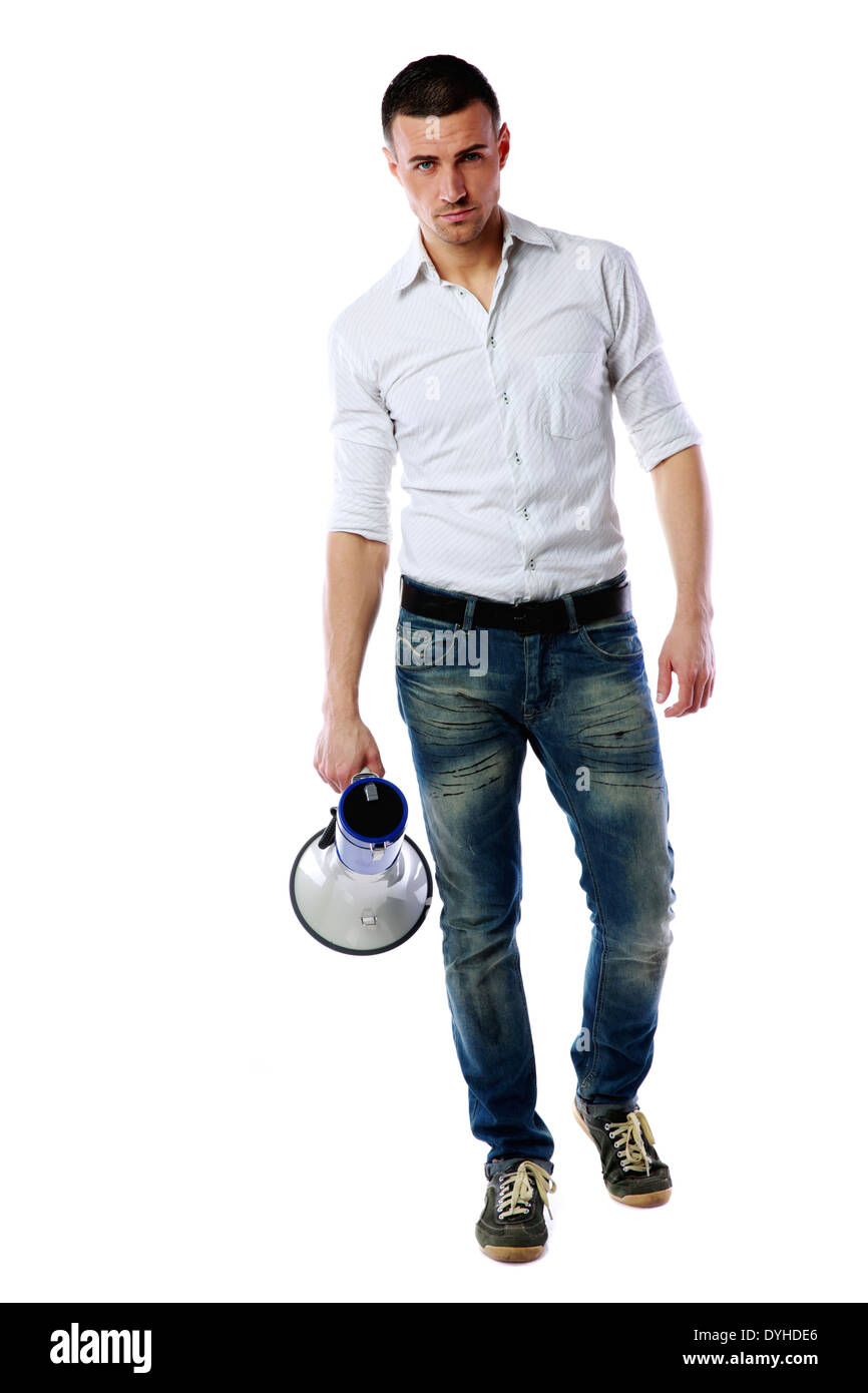 Confident man standing with megaphone over white background - Stock Image