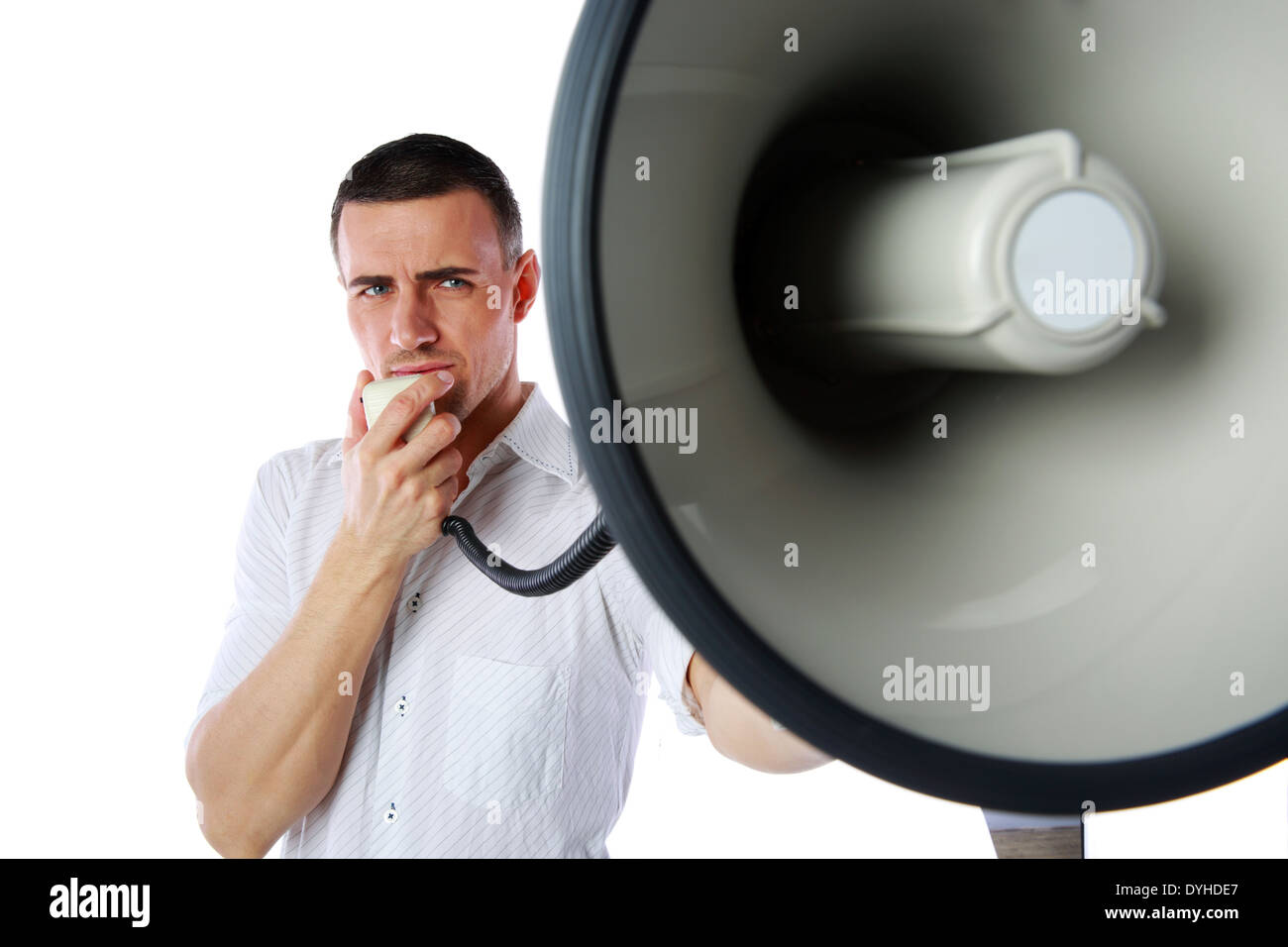Portrait of a man roaring loudly into megaphone over white background - Stock Image