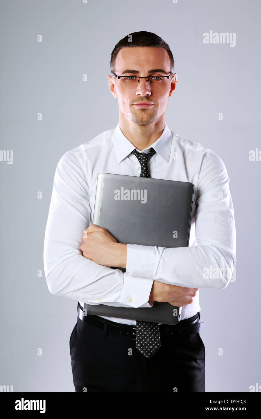 Portrait of a businessman with laptop on gray background - Stock Image