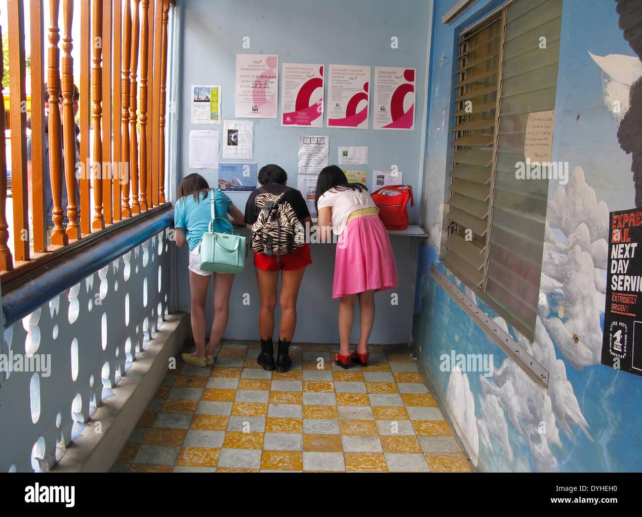 Isla Culebra Puerto Rico USA territory three Chinese tourist girls write postcards at Culebra Postoffice - Stock Image