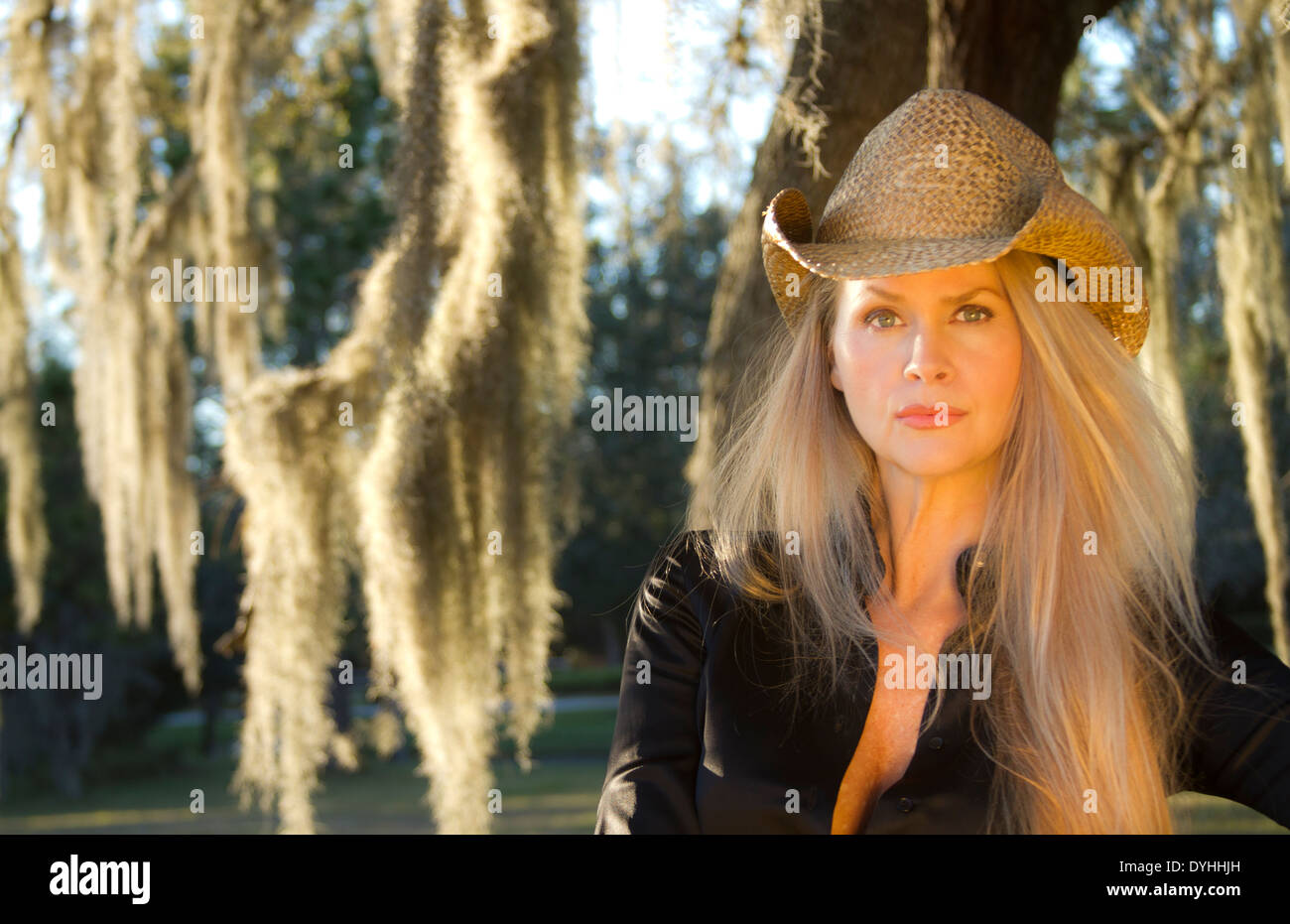 beautiful blonde middle aged woman cowgirl with cowboy hat on - Stock Image e38b582501b6