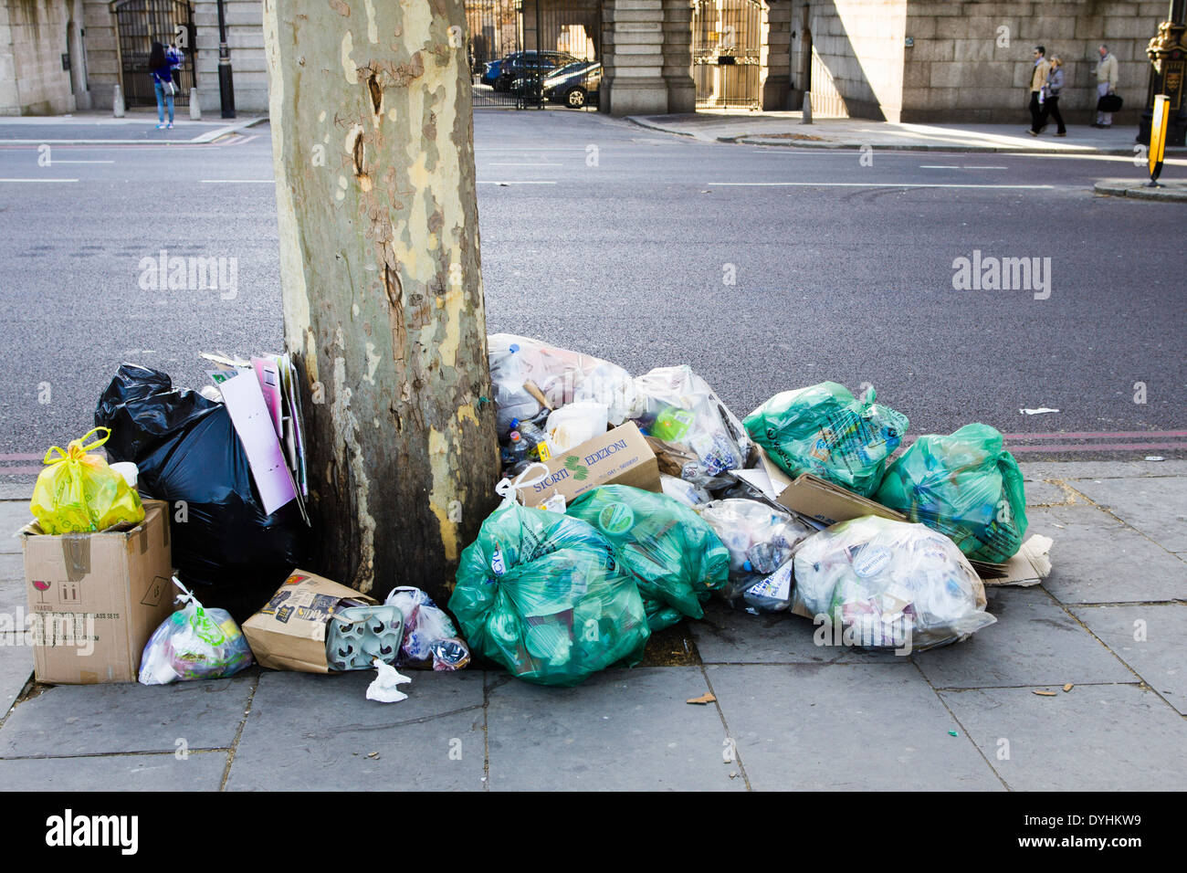 Rubbish/trash heaped up in bags under a tree on a pavemnet, London, England, UK - Stock Image
