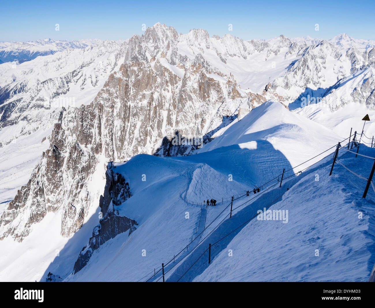 Roped path route to Vallee Blanche with skiers descending on Aiguille du Midi. Chamonix-Mont-Blanc Rhone-Alpes France - Stock Image