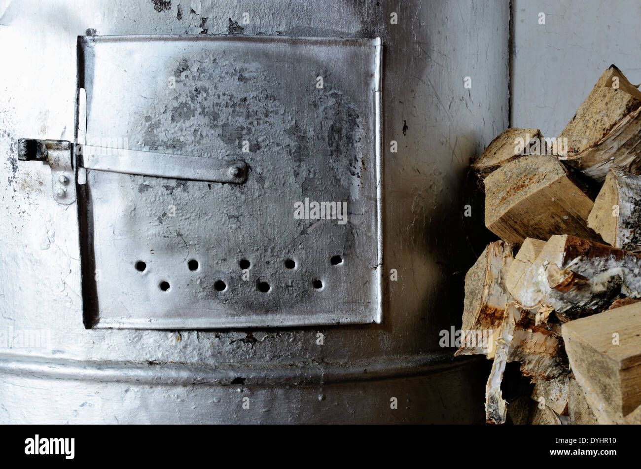 old stove and birch firewood, horizontal photo - Stock Image