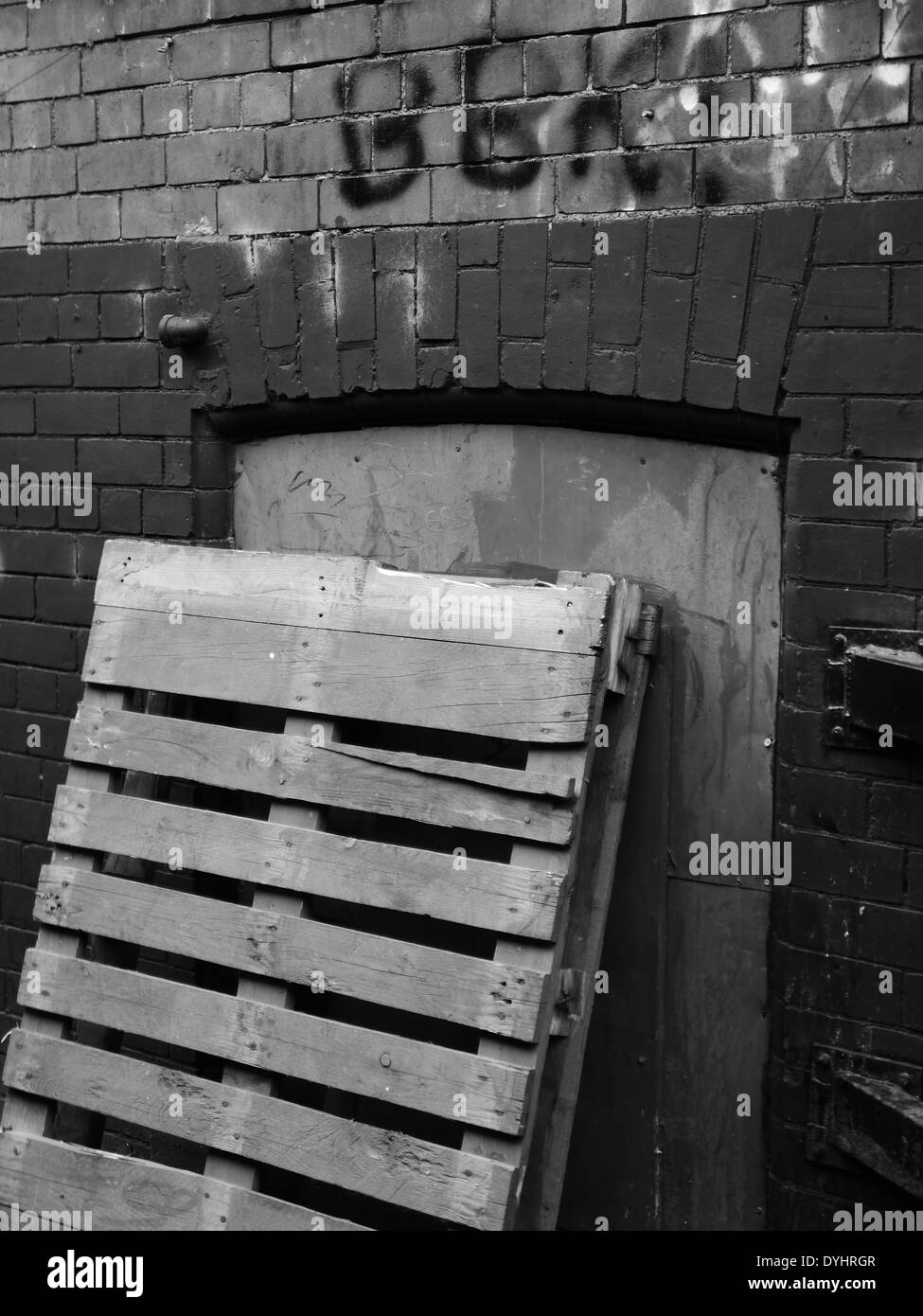 Monochrome image - Urban street scene, showing discarded wooden pallet leaning against a wall, Newcastle upon Tyne, England, UK - Stock Image