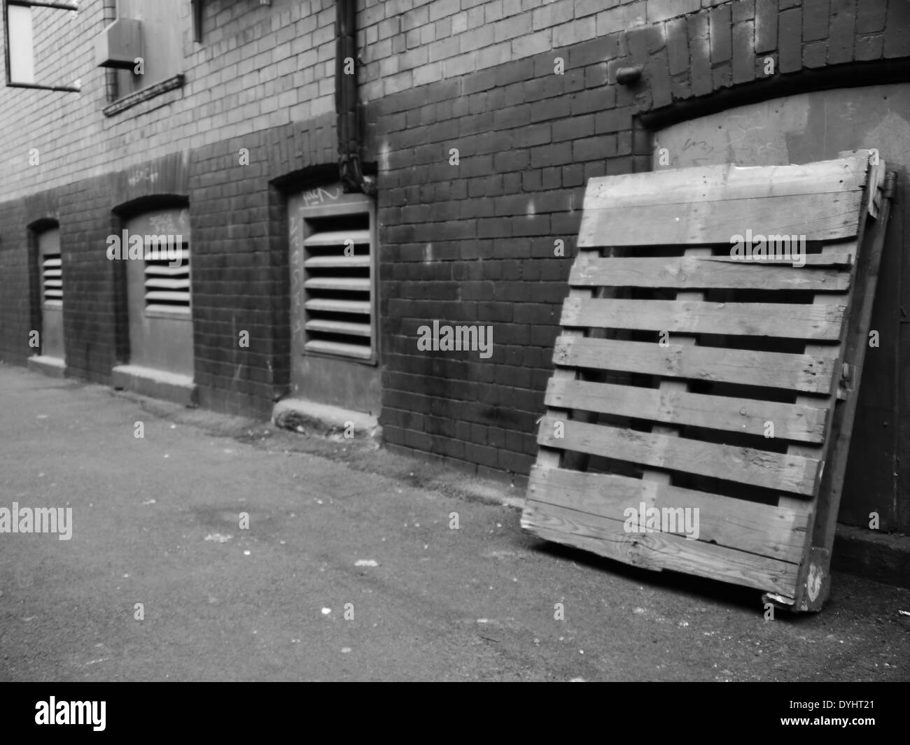 Monochrome image - Urban street scene showing alley with wooden pallet, and ventilation doors, Newcastle upon Tyne, England, UK - Stock Image