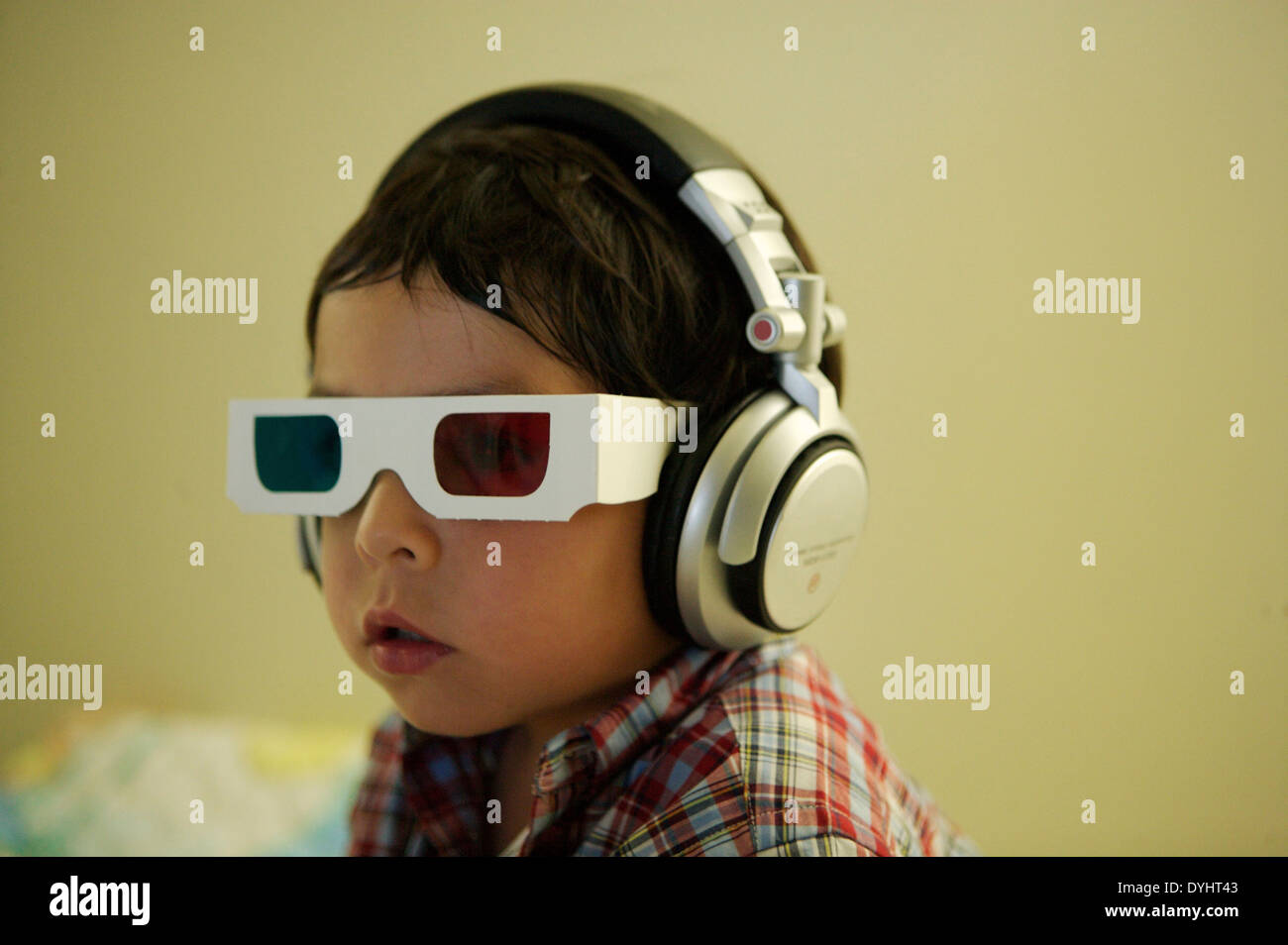 Small Boy Wearing 3-D Glasses and Headphones - Stock Image