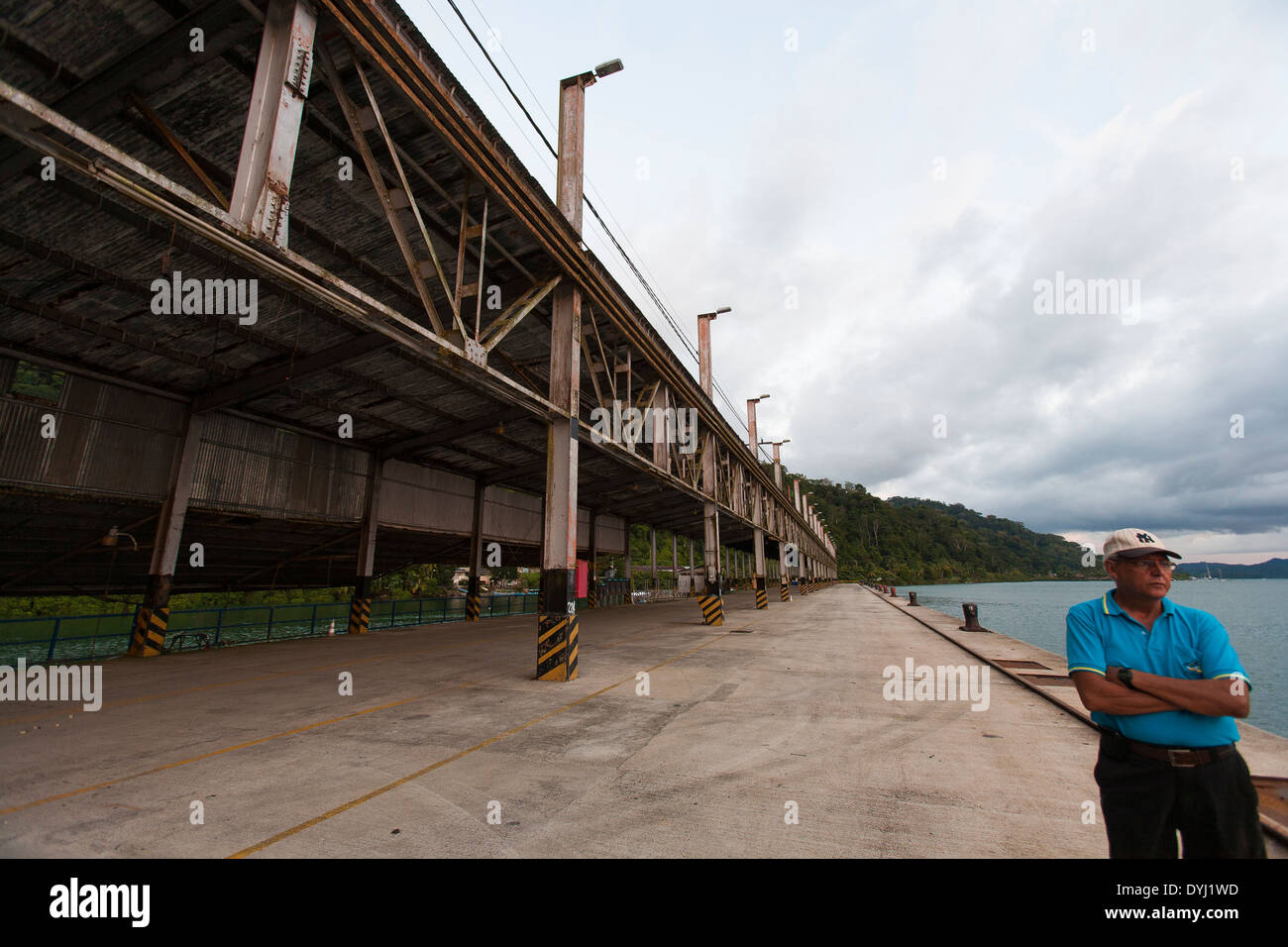A Costa Rican man stands with his arms folded on the commercial dock at the port of Golfito in the southern zone of Costa Rica - Stock Image