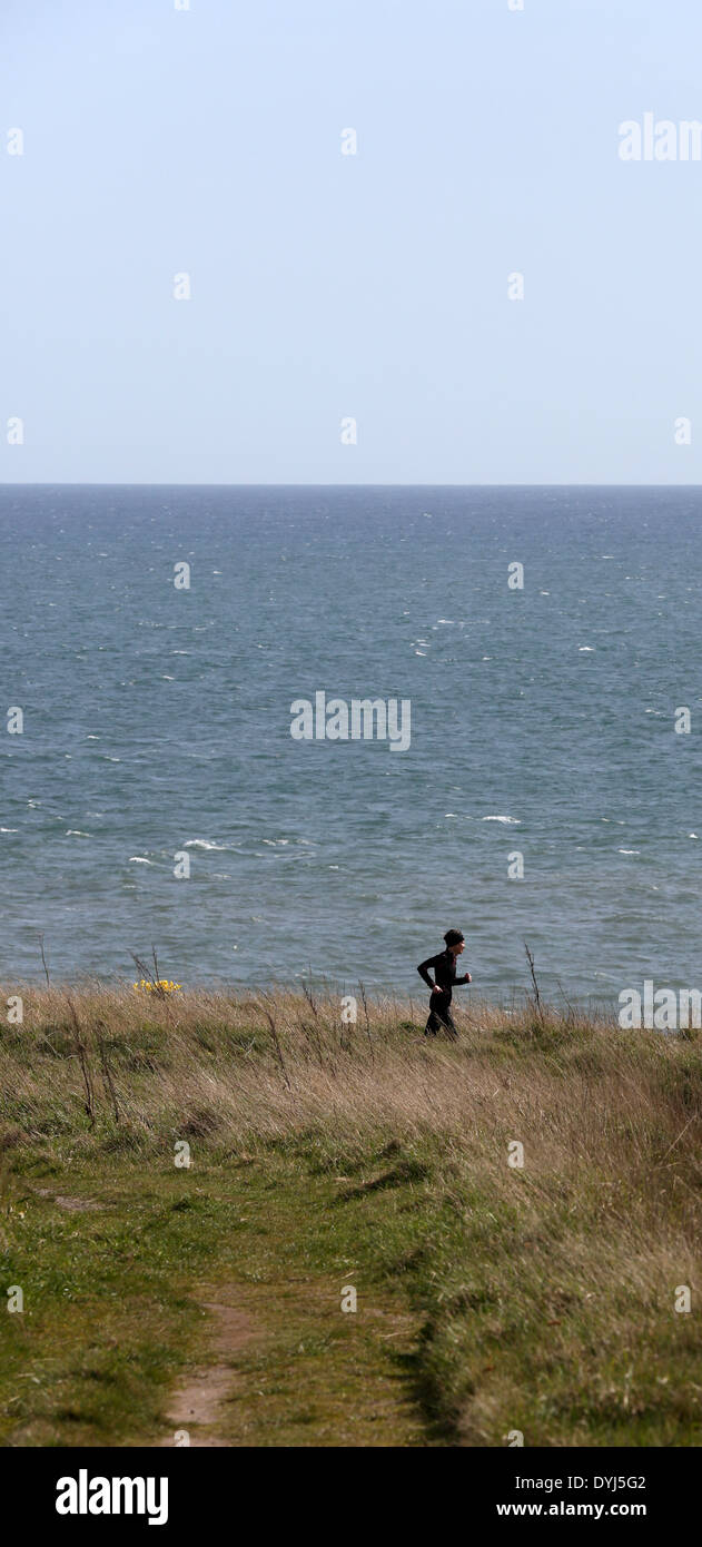Runner on the coastal Path at Cove Bay, Aberdeen city, Scotland, UK, with the North Sea in the background - Stock Image