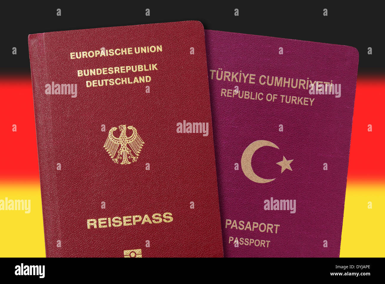 German and Turkish passport in front Germany flag, dual citizenship - Stock Image