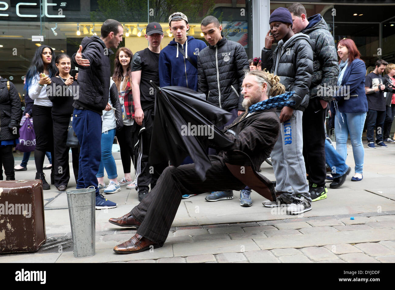 Manchester, UK. 19th April 2014. A young man tries to explain to his friends how a gravity-defying street performer Stock Photo